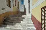 Fototapeta Na drzwi - Steps of stairs leading to the top on the street of a Greek village on the island of Symi. Greece © Oleg