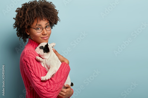 Leinwanddruck Bild Sideways shot of calm tender woman holds small sleepy puppy closely to chest, snuggles french bulldog wears round spectacles, carries dog for having outdoor walk. Friendship between people and animals