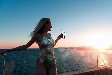 girl in a bathing suit looks at a beautiful sunset over the sea © Mikhaylovskiy