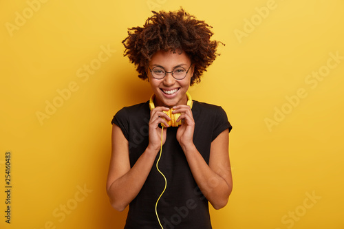 Leinwanddruck Bild Isolated shot of optimistic woman with curly hairstyle, wears black t shirt and spectacles, feels good from spare time, enjoys listening audio book, likes hobby, being real meloman of pop music