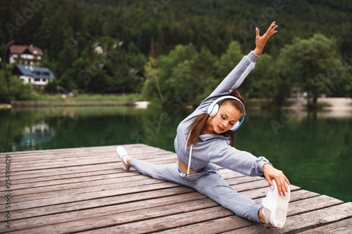 Young sports woman stretching legs at dock on the lake in the mountains - 254164629
