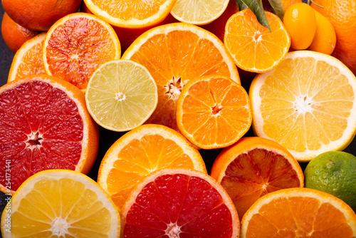 Leinwanddruck Bild Sliced citrus fruits in the foreground
