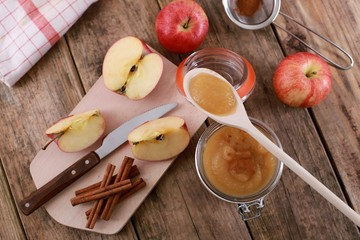 homemade apple jam , apple puree, with cinnamon, fresh apples and a wooden spoon on wooden rustic table
