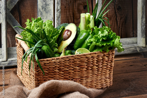 Green vegetables and fruits and greens in a brown wicker basket on a wooden background. Healthy eating concept - 254181046
