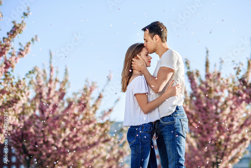 Leinwanddruck Bild Passion and love concept. Man and woman kissing in blooming garden on spring day. Couple hugs near sakura trees. Couple in love spend time in spring garden.