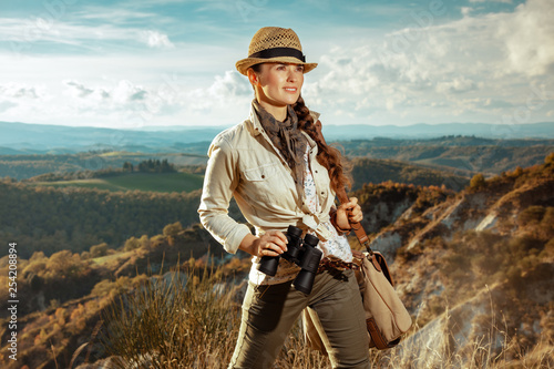 solo traveller woman with binoculars looking into the distance