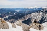 Skitourengeher sitz auf einem Fels und genießt die Aussicht