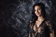portrait of sexy beautiful smiling woman in lace black sensual lingerie with long curly hair posing in studio.