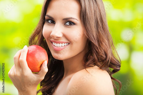 Leinwandbild Motiv Young happy smiling woman with apple, outdoors
