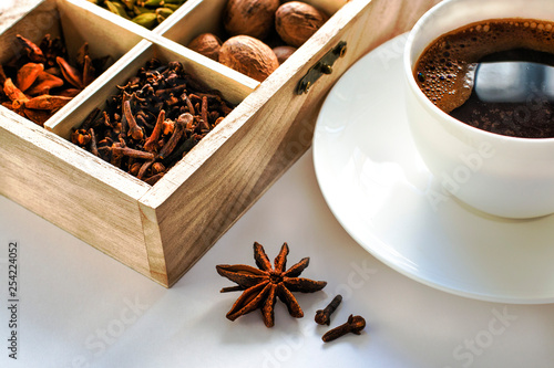 still life with black coffee in a white cup and a wooden box with spices © Olga