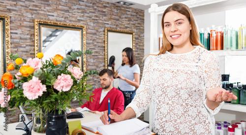 Leinwanddruck Bild Portrait of young woman  administrator inviting to beauty salon