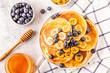 Leinwandbild Motiv Pancakes with banana,  blueberries on white plate.
