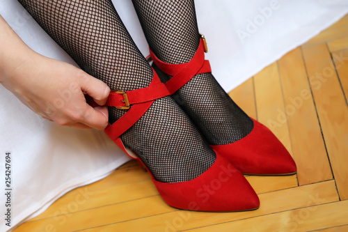 Sexy female feet in red velvet shoes on high heels. Woman unbuttons shoes, girl in black fishnet stockings in the bedroom, female fashion