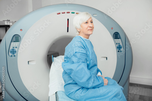 Pensive elderly woman sitting on scanner table. waiting for CT scan