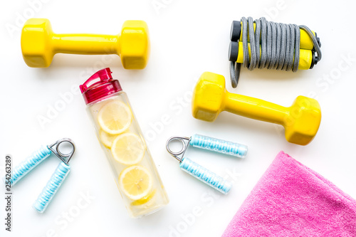 workout with bars, bottle of water and wrist builder yellow background top view