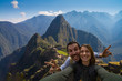 Leinwanddruck Bild - Happy couple backpackers traveling in front of Machu Picchu. taking selfie in front of the ruins of the ancient city. Cusco, Peru travel
