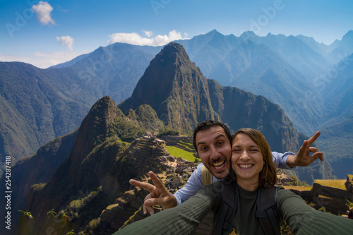 Leinwanddruck Bild Happy couple backpackers traveling in front of Machu Picchu. taking selfie in front of the ruins of the ancient city. Cusco, Peru travel
