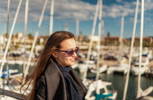 Businesswoman in sunglasses walking with a lot of yachts and boats behind.