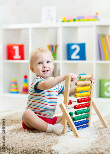 Cute child boy plays with abacus in nursery - 254306668