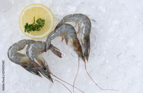 Leinwandbild Motiv Fresh raw shrimps prawns and lemon on ice background in the seafood supermarket
