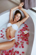 Body skin care. Woman at spa relaxing in bath with milk, flowers