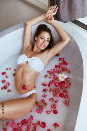 Leinwandbild Motiv Body skin care. Woman at spa relaxing in bath with milk, flowers