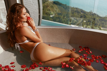 Woman in spa taking bath with flowers. Girl relaxing in bath tub © puhhha