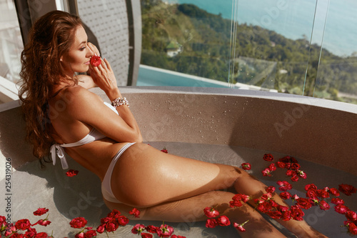 Leinwanddruck Bild Woman in spa taking bath with flowers. Girl relaxing in bath tub