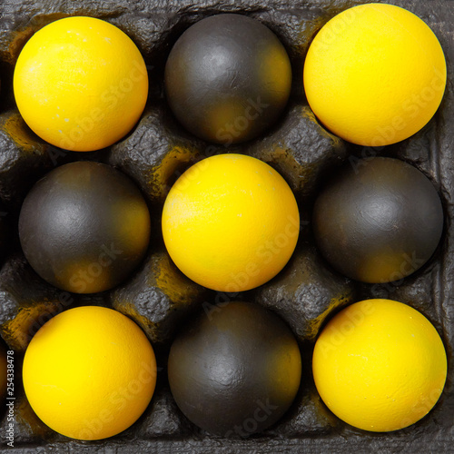 Closeup composition of multicolored yellow black eggs in the form of a pattern in a black cardboard box. Easter background. Flat lay © artjazz