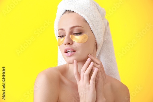 Leinwanddruck Bild Young woman with under-eye patches on color background