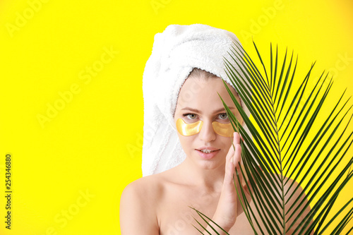 Leinwanddruck Bild Young woman with under-eye patches and tropical leaf on color background