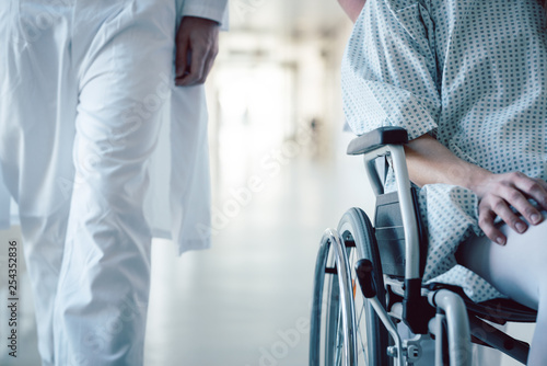 Leinwanddruck Bild Doctor and nurse pushing wheelchair with patient in hospital