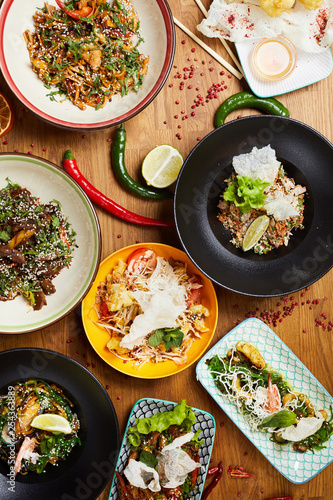 Above view composition of several Asian food dishes on wooden background, copy space - 254363889