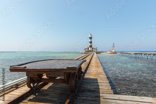 Railcart on pier with lighthouse - 254364240