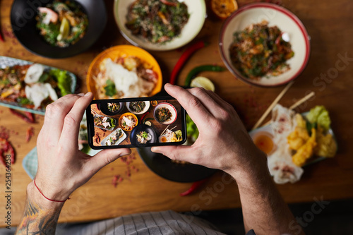 Leinwanddruck Bild Above view closeup of unrecognizable man taking picture of Asian food dishes, copy space