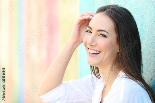 Happy woman with perfect smile in a colorful background