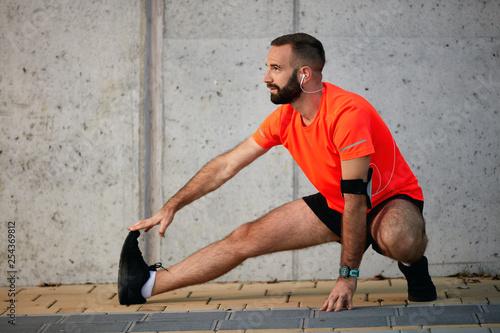 Leinwanddruck Bild Sporty man stretching legs before running. Healthy lifestyle concept.