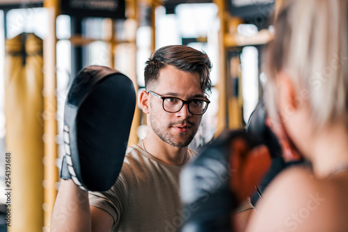Male trainer exercising with young sportswoman in boxing gloves at gym. - 254393688