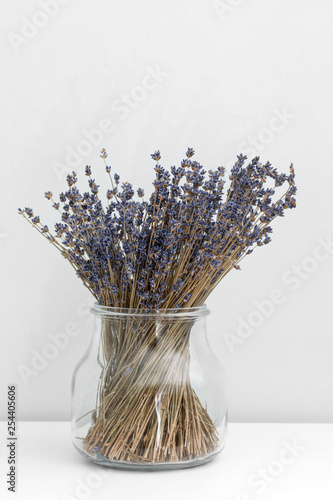 Lavender flowers in glass vase, white wooden background, spa concept, aromatherapy. Lavender flowers in close up - 254405606