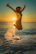 Happy woman jumping in the sea