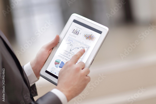 Leinwanddruck Bild Close up of Man's hands working with digital tablet, Financial