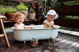 Small children with a drink sitting in bath outdoors in garden in summer.