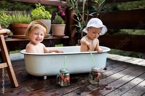 Leinwandbild Motiv Small children with a drink sitting in bath outdoors in garden in summer.