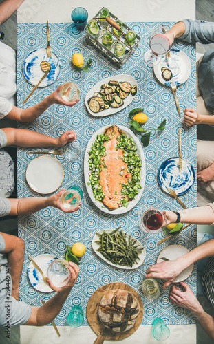 Mediterranean style dinner. Flat-lay of table with cooked salmon, starters, bread, lemonade over blue table cloth with hands holding drinks, top view, vertical composition. Holiday party concept © sonyakamoz