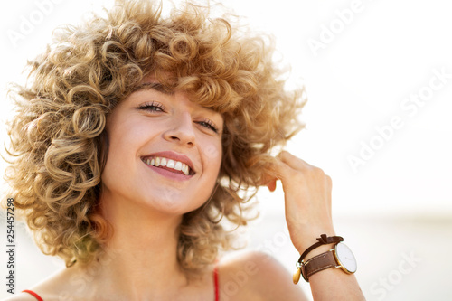 Portrait of young woman with curly hair - 254457298