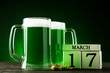St. Patrick's Day. Green beer in mugs with cube calendar and wheat ears on dark background