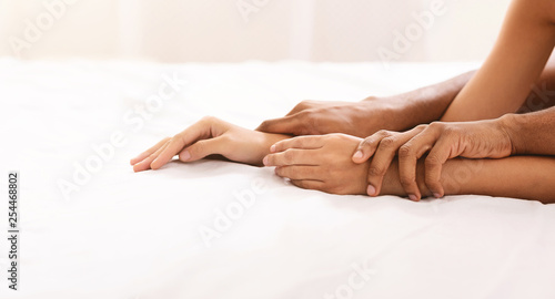 Black man and woman hands having sex on bed - 254468802