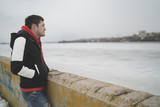 Handsome guy in a jacket on the dock in the spring of posing on the background of the water. The man on the waterfront