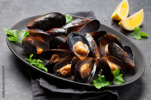 Delicious mussels with tomato sauce and parsley - 254478259