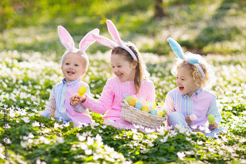 Kids with bunny ears on Easter egg hunt. - 254481427